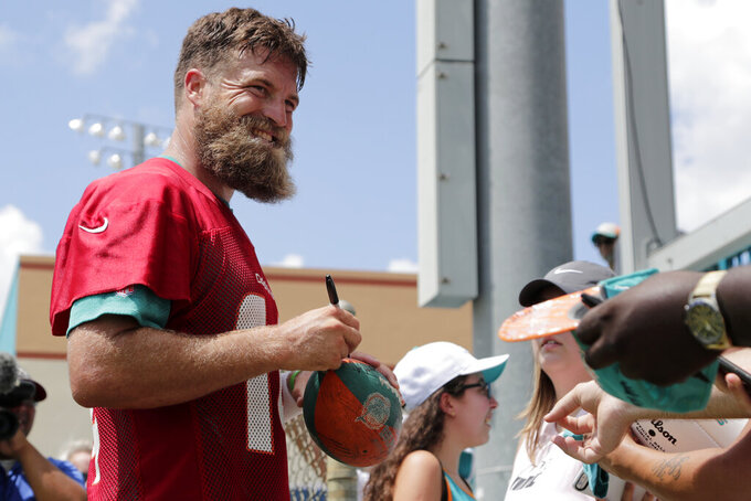 Miami Dolphins quarterback Ryan Fitzpatrick signs autographs during NFL football training camp,Thursday, July 25, 2019, in Davie, Fla. (AP Photo/Lynne Sladky)