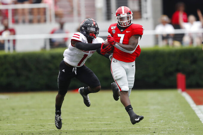 Georgia running back D'Andre Swift (7) tries to escape from Arkansas State cornerback Jerry Jacobs (1) in the first half of an NCAA college football game Saturday, Sept. 14, 2019, in Athens, Ga. (AP Photo/John Bazemore)