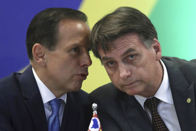 FILE - In this Nov. 14, 2018, file photo, Brazil's President-elect Jair Bolsonaro, right, listens to Sao Paulo's Governor-elect Joao Doria, during a meeting in Brasilia, Brazil. As governor, Doria has become one of the nation's foremost advocates of strong restrictions on daily life to contain the virus, such as closing schools and restricting commerce and public transportation. That's put him squarely in Bolsonaro's line of fire. (AP Photo/Eraldo Peres, File)