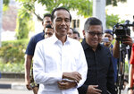 Incumbent Indonesian President Joko Widodo, center, walks with the Secretary General of Indonesian Democratic Party-Struggle Hasto Kristiyanto, right, upon arrival for a meeting with leaders of his coalition parties in Jakarta, Indonesia, Thursday, April 18, 2019. Widodo said Thursday he was won re-election after receiving an estimated 54% of the vote, backtracking on an earlier vow to wait for official results after his challenger made improbable claims of victory. (AP Photo/Achmad Ibrahim)