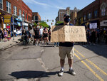 A demonstrator holds up a sign while standing in the middle of State Street during a peaceful protest in Ann Arbor, Mich. on Tuesday, June 2, 2020. Ann Arbor police chief Michael Cox and other officers walked with demonstrators. (Jenna Kieser/Ann Arbor News via AP)