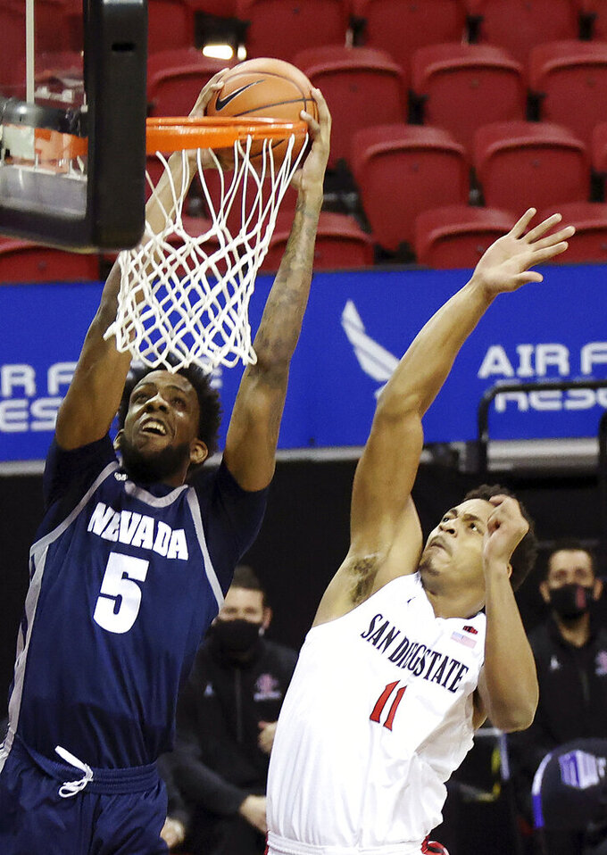 Nevada forward Warren Washington (5) dunks as San Diego State forward Matt Mitchell (11) defends during the first half of an NCAA college basketball game in the semifinal round of the Mountain West Conference men's tournament Friday, March 12, 2021, in Las Vegas. (AP Photo/Isaac Brekken)