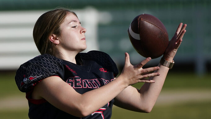 Sam Gordon catches a football on Oct. 20, 2020, in Herriman, Utah. Gordon was the only girl in a tackle football league when she started playing the game at age 9. Now, Gordon hopes she can give girls a chance to play on female-only high school teams through a lawsuit. (AP Photo/Rick Bowmer)