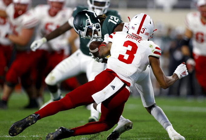 Michigan State's Chester Kimbrough (12) intercepts a Nebraska pass intended for Nebraska's Samori Toure (3) during overtime of an NCAA college football game, Saturday, Sept. 25, 2021, in East Lansing, Mich. (AP Photo/Al Goldis)