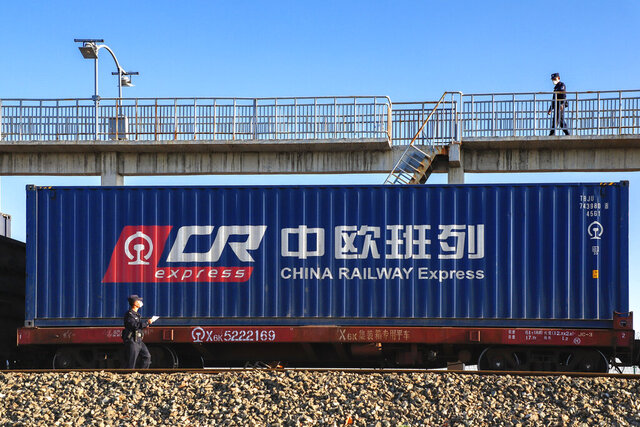 In this April 20, 2020, photo, policemen wearing face masks inspect a cargo train at a land cargo port on the border between China and Kazakhstan in Horgos in northwestern China's Xinjiang Uyghur Autonomous Region. China's exports rebounded in April to rise 3.5% over a year earlier, but forecasters warned that strength is unlikely to last as the coronavirus pandemic depresses global consumer demand. (Chinatopix via AP)
