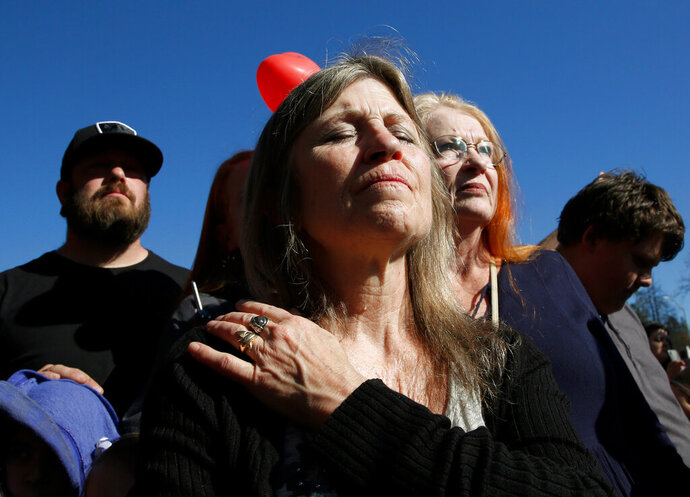 Tami Neves closes her eyes during ceremonies of the one year anniversary of the Camp Fire, held in Paradise, Calif., Friday, Nov. 8, 2019. Neves lost her business in the fire and other family members lost their homes. (AP Photo/Rich Pedroncelli)