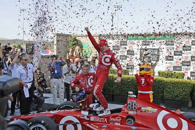 FILE - In this Aug. 30, 2015, file photo, Scott Dixon, of New Zealand, celebrates atop his car after winning the IndyCar Grand Prix of Sonoma auto race and IndyCar championship, in Sonoma, Calif. Chip Ganassi knew Scott Dixon as a quiet kid in a paddock full of superstars when he hired him four races into the 2002 season. The pairing has since produced the most celebrated driver of his generation. (AP Photo/Eric Risberg, File)