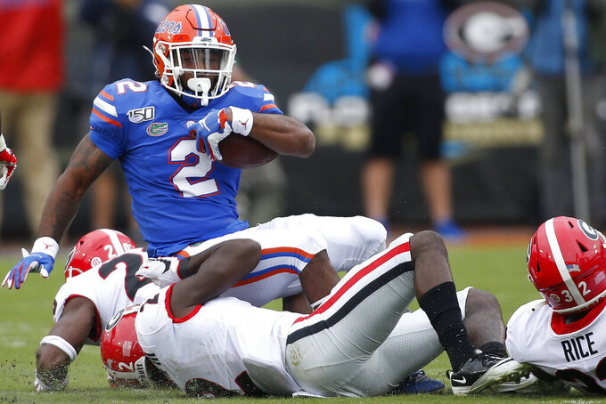 Florida running back Lamical Perine (2) is taken down by Georgia defensive back Richard LeCounte (2) in the first half of an NCAA college football game Saturday, Nov. 2, 2019, in Jacksonville, Fla. Georgia won 24-17.  (Joshua L. Jones/Athens Banner-Herald via AP)