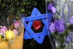 FILE - In this Nov. 20, 2018 file photo, a Star of David fashioned from popsicle sticks hangs from bushes outside the Tree of Life Synagogue in Pittsburgh. One-third of the attackers who terrorized schools, houses of worship or businesses nationwide last year had a history of serious domestic violence, two-thirds had mental health issues, and nearly all had made threatening or concerning communications that worried others before they struck, according to a U.S. Secret Service report on mass attacks. (AP Photo/Gene J. Puskar, File)