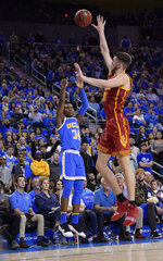 UCLA guard David Singleton, left, hits a 3-point shot from the corner as Southern California forward Nick Rakocevic defends during overtime in an NCAA college basketball game Thursday, Feb. 28, 2019, in Los Angeles. UCLA won 93-88. (AP Photo/Mark J. Terrill)