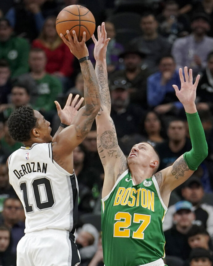 San Antonio Spurs' DeMar DeRozan (10) shoots against Boston Celtics' Daniel Theis during the first half of an NBA basketball game, Monday, Dec. 31, 2018, in San Antonio. (AP Photo/Darren Abate)