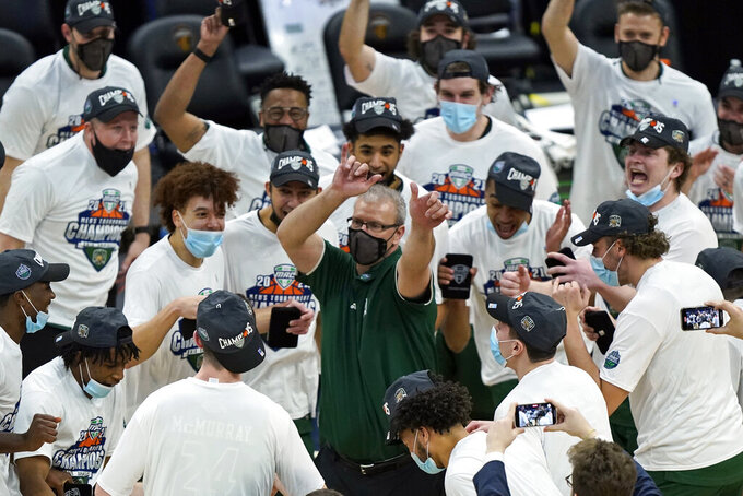 Ohio head coach Jeff Boals, center, celebrates with players after they defeated Buffalo in an NCAA college basketball game in the championship of the Mid-American Conference tournament, Saturday, March 13, 2021, in Cleveland. (AP Photo/Tony Dejak)