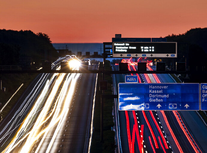 File---Picture taken June 14, 2019 shows cars and trucks driving on a highway just before the sun rises in Frankfurt, Germany. (AP Photo/Michael Probst)