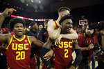 Southern California guard Jonah Mathews (2) is hugged by teammates after making a game-winning 3-point basket at the end of an NCAA college basketball game against UCLA Saturday, March 7, 2020, in Los Angeles. (AP Photo/Marcio Jose Sanchez)d