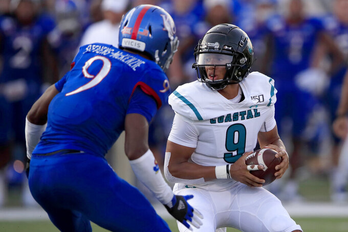 Kansas linebacker Najee Stevens-McKenzie, left, moves in to sack Coastal Carolina quarterback Fred Payton, right, during the first half of an NCAA college football game in Lawrence, Kan., Saturday, Sept. 7, 2019. (AP Photo/Orlin Wagner)