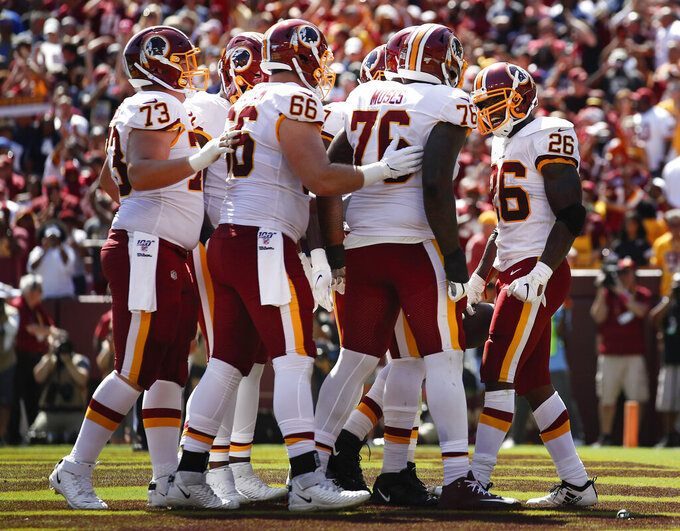 Washington Redskins running back Adrian Peterson (26) celebrates his touchdown against the Dallas Cowboys with his teammates in the first half of an NFL football game, Sunday, Sept. 15, 2019, in Landover, Md. (AP Photo/Alex Brandon)
