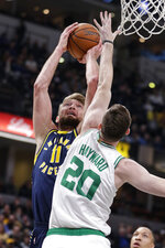 Indiana Pacers forward Domantas Sabonis (11) shoots over Boston Celtics forward Gordon Hayward (20) during the first half of an NBA basketball game in Indianapolis, Wednesday, Dec. 11, 2019. (AP Photo/Michael Conroy)
