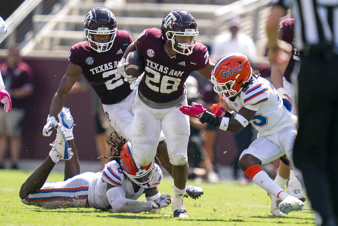 Texas A&M running back Isaiah Spiller (28) stiff arms Florida defensive back Chester Kimbrough (25) during a run during the second half of an NCAA college football game, Saturday, Oct. 10, 2020. in College Station, Texas. (AP Photo/Sam Craft)