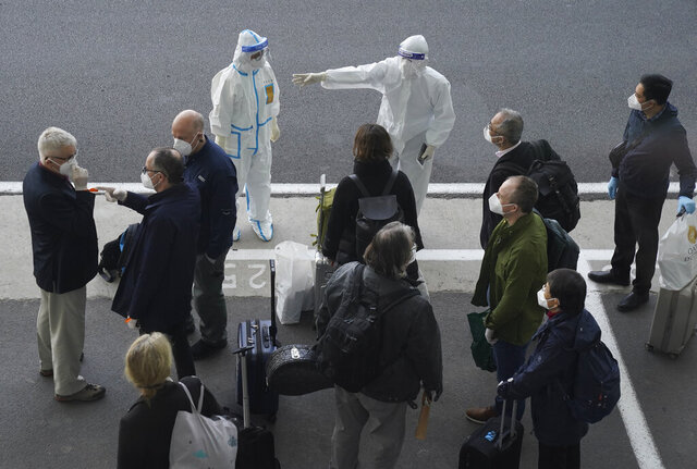 A worker in protective coverings directs members of the World Health Organization (WHO) team on their arrival at the airport in Wuhan in central China's Hubei province on Thursday, Jan. 14, 2021. A global team of researchers arrived Thursday in the Chinese city where the coronavirus pandemic was first detected to conduct a politically sensitive investigation into its origins amid uncertainty about whether Beijing might try to prevent embarrassing discoveries. (AP Photo/Ng Han Guan)