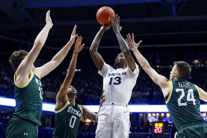 Xavier  forward Naji Marshall (13) shoots against Siena guard Jimmy Ratliff (24) the first half of an NCAA college basketball game Friday, Nov. 8, 2019, in Cincinnati. (AP Photo/John Minchillo)