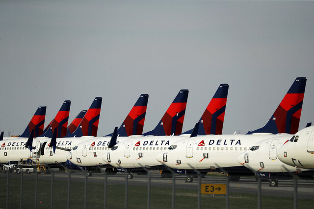 FILE - In this April 1, 2020 file photo, several dozen mothballed Delta Air Lines jets are parked at Kansas City International Airport in Kansas City, Mo.   Shares in major U.S. airlines were poised for gains Wednesday, Oct. 7,  after President Donald Trump tweeted his support for a $25 billion relief package for the struggling industry and prodded Congress to take action. Airline stocks rose anywhere from 1% to 5% in premarket trading.(AP Photo/Charlie Riedel, File)