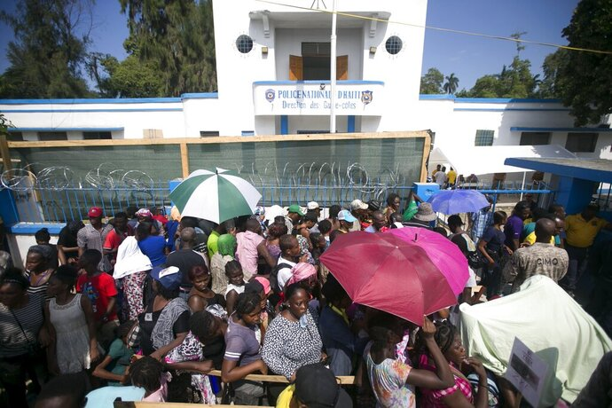 Patients line up outside the Killick Coast Guard Base to meet with U.S. military doctors who arrived on the Navy's hospital ship USNS Comfort anchored off Port-au-Prince, Haiti, Friday, Nov. 8, 2019. The visit of the hospital ship comes as violent demonstrations and street barricades have led several hospitals across the country to run out of medical supplies and some have temporarily closed as protesters keep demanding the president's resignation. (AP Photo/Dieu Nalio Chery)