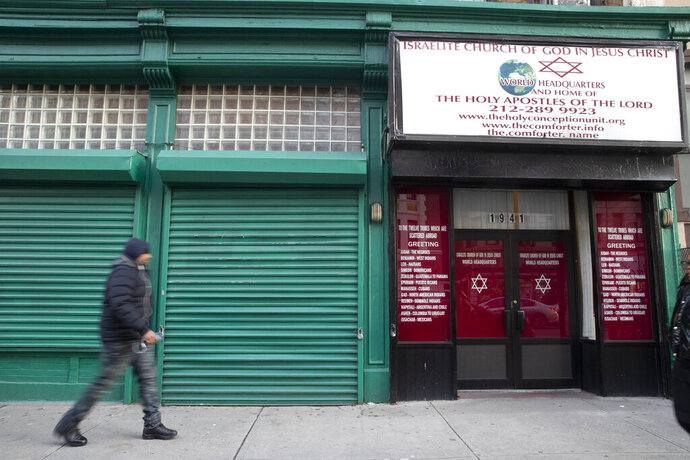 A pedestrian walks past the world headquarters of the Israelite Church of God in Jesus Christ, Thursday, Dec. 12, 2019, in the Harlem neighborhood of New York. (AP Photo/Mary Altaffer)