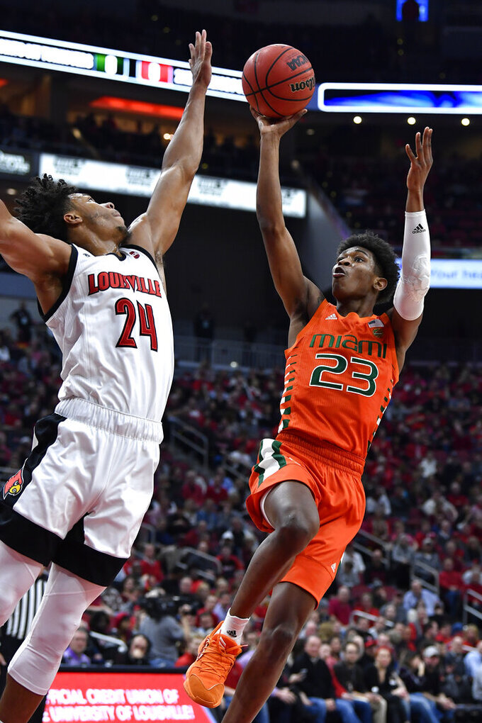 Miami guard Kameron McGusty (23) shoots as Louisville forward Dwayne Sutton (24) defends during the first half of an NCAA college basketball game in Louisville, Ky., Tuesday, Jan. 7, 2020. (AP Photo/Timothy D. Easley)