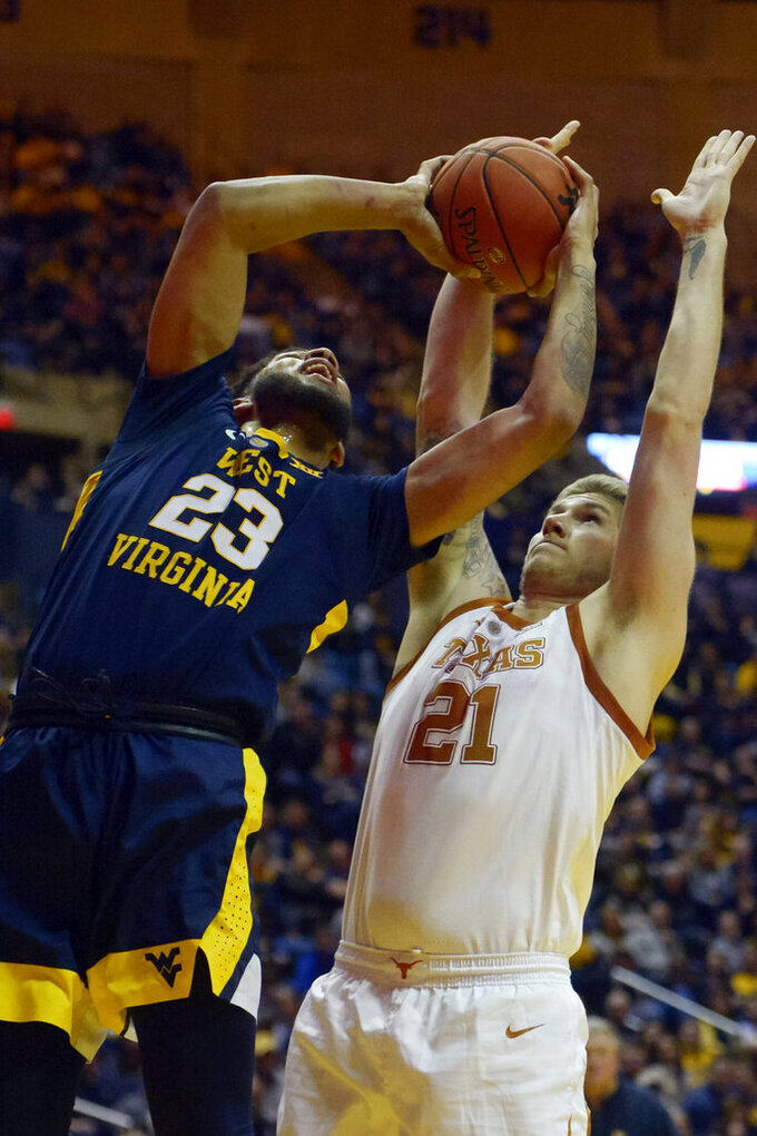 Texas forward Dylan Osetkowski (21) attempts to block West Virginia  forward Esa Ahmad (23) during the second half of an NCAA college basketball game in Morgantown, W.Va., Saturday, Feb. 9, 2019. (AP Photo/Craig Hudson)