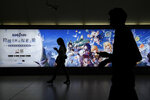 Commuters walk by a computer and mobile phone's RPG games advertised at a subway station in Beijing Tuesday, Sept. 14, 2021. Chinese regulators have set up a platform that allows the public to report on gaming companies they believe are violating restrictions on online game times for children. (AP Photo/Andy Wong)