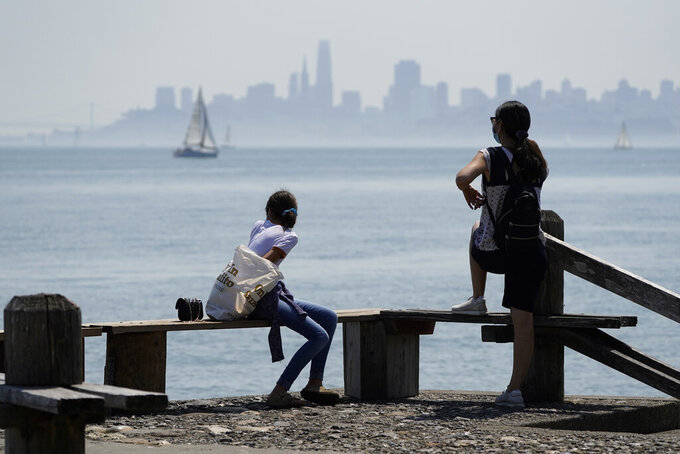 People look out at the view of San Francisco Bay Saturday, Sept. 5, 2020, in Sausalito, Calif. California is sweltering under a dangerous Labor Day weekend heat wave that was expected to spread triple-digit temperatures over much of the state while throngs of people might spread the coronavirus by packing beaches and mountains for relief. (AP Photo/Eric Risberg)