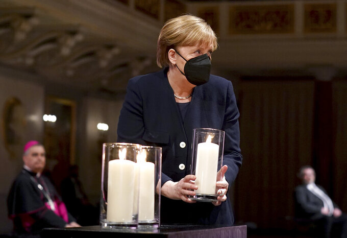 German Chancellor Angela Merkel holds a candle during a memorial service in Berlin, Germany, Sunday, April 18, 2021 in remembrance of Germany's corona dead. (AP Photo/Michael Sohn, pool)