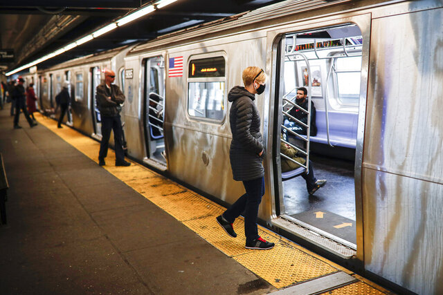 Riders, some wearing masks and gloves as a protective measure over coronavirus concerns, enter a New York City subway train Tuesday, April 7, 2020, in New York. (AP Photo/John Minchillo)