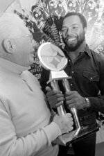 """FILE - Pittsburgh Steelers strong safety Donnie Shell, right, accepts the trophy for being named the Steelers' Most Valuable Player, from team vice president and chairman of the board Art Rooney, in Pittsburgh, in this Dec. 16, 1980, file photo. """"Chuck Noll had that saying, 'Whatever it takes' and Donnie was kind of the definition of that,"""" Steelers president Art Rooney II said. The hard-hitting cornerback won four Super Bowls during his 14 years in the NFL and next month will become the fifth — and most unlikely — member of the """"Steel Curtain"""" defense to be enshrined in Canton.(AP Photo/Gene Puskar, File)"""