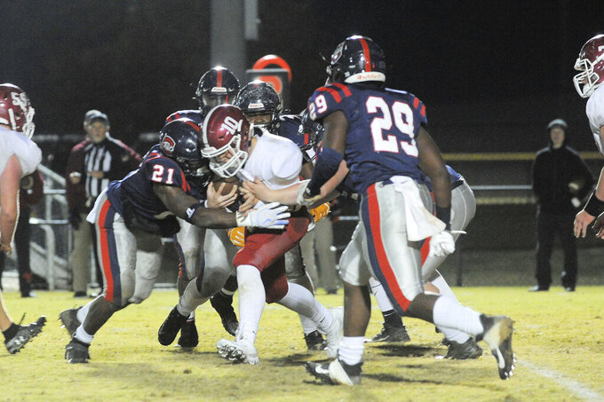 In this photo provided by Mike Pettus, Central of Clay County High School's J.D. McNealey (21) tackles a Sardis High School player during a football game in Lineville, Ala., Friday, Nov. 8, 2019. At Central of Clay County High School in Alabama, small-town football is thriving. The team has helped bond two communities that were once fierce rivals, then reluctant partners, and now proud supporters of a two-time Class 5A state football champions. (Mike Pettus via AP)