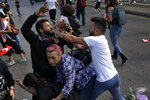 FILE - In this Oct. 29, 2019 file photo, a Hezbollah supporter, right, clashes with an anti-government protester, left, during a protest in Beirut, Lebanon. An economic meltdown, a revolution, financial collapse, a virus outbreak and a cataclysmic explosion that virtually wiped out the country's main port. The past year has been nothing short of an earthquake for tiny Lebanon, with an economic meltdown, mass protests, financial collapse, a virus outbreak and a cataclysmic explosion that virtually wiped out the country's main port. Yet Lebanese fear even darker days are ahead. (AP Photo/Bilal Hussein, File)