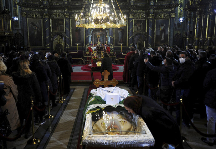 A woman kisses a protective screen over the coffin of Patriarch Irinej as he lies in repose at the Congregational church in Belgrade, Serbia, Saturday, Nov. 21, 2020. Mourners flocked to pay respects following the death of the Serbian Orthodox Church Patriarch Irinej, many ignoring preventive measures against the new coronavirus even though the head of the church died after contracting the virus himself. (AP Photo/Ana Paunkovic)