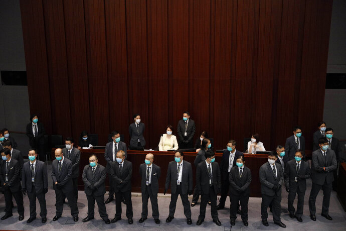 Pro-Beijing politician, Starry Lee, center, surrounded by security guards as she attends a Legislative Council's House Committee meeting, in Hong Kong, Friday, May 8, 2020. Scuffles also broke out when Lee called the meeting to order, with pro-democracy lawmakers rushing the table as security shoved back. Security guards physically carried out pro-democracy lawmakers Chu Hoi Dick and Ray Chan, who were ordered to leave due to disorderly conduct. (AP Photo/Kin Cheung)