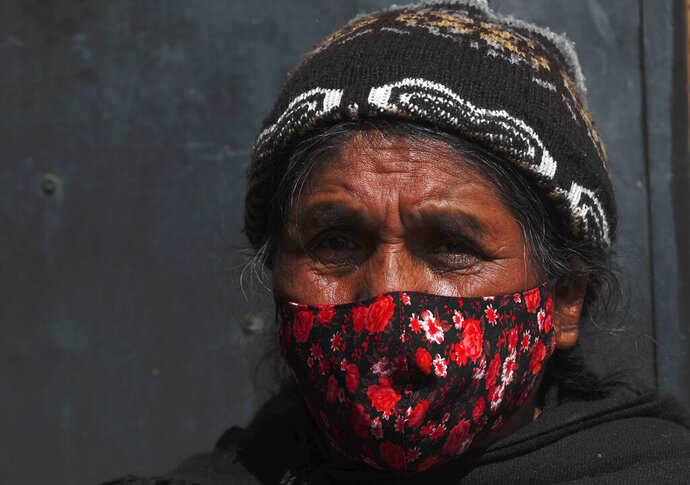 A woman wearing a protective face mask speaks with healthcare workers during a house-to-house campaign to help curb the spread of the new coronavirus, in the Mallasa neighborhood of La Paz, Bolivia, Saturday, Aug. 8, 2020. (AP Photo/Juan Karita)
