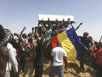 Mourners chanting with the coffin of one of the victims who was killed this week during his funeral at a cemetery in N'Djamena, Chad, Saturday, May 1, 2021. Hundreds of chanting mourners carrying Chadian flags gathered Saturday to bury victims who were shot dead earlier this week amid demonstrations against the country's new military government .(AP Photo/Sunday Alamba)