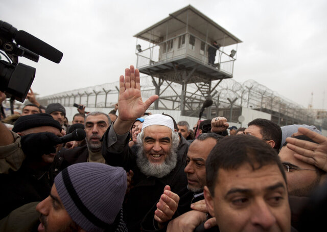 """FILE - In this Dec. 12, 2010 file photo, Sheik Raed Salah, head of the outlawed northern branch of the Islamic Movement in Israell, center, waves after his release from Ayalon prison at the central Israeli town of Ramle. An Israeli court on Monday, Feb. 10, 2020, sentenced Salah to 28 months in prison for """"inciting to terror"""" in a series of speeches he made after a deadly attack in 2017 on Israeli police at a contested Jerusalem holy site. Salah was convicted in November on incitement charges for exhorting others to follow the example of the gunmen who killed the two Israeli policemen in that attack. (AP Photo/Oded Balilty, File)"""