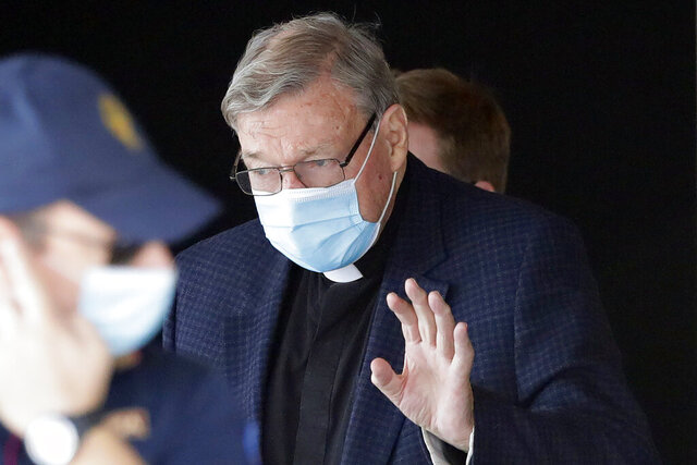 FILE - In this Sept. 30, 2020, file photo, Australian Cardinal George Pell waves as he arrives at Rome's international airport in Fiumicino. Australian state police said Friday, Oct. 23, 2020 it was not investigating the transfer of money from the Vatican to Australia, throwing doubt on Italian media speculation that it might be linked to the overturned convictions of Cardinal George Pell for child sex abuse. (AP Photo/Andrew Medichini, File)