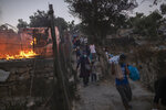Refugees and migrants carrying their belongings flee a fire burning at the Moria camp on Lesbos island, Greece, Wednesday, Sept. 9, 2020. Fire struck for second day in Greece's notoriously overcrowded refugee camp, leaving more than 12,000 people in need of emergency shelter. (AP Photo/Petros Giannakouris)