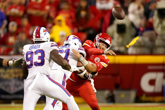 Kansas City Chiefs quarterback Patrick Mahomes, right, throws under pressure from Buffalo Bills defensive tackle Justin Zimmer and defensive end Efe Obada (93) during the second half of an NFL football game Sunday, Oct. 10, 2021, in Kansas City, Mo. (AP Photo/Charlie Riedel)