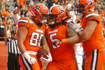 Syracuse's Aaron Hackett, left, celebrates with teammates Chris Elmore, center, and Carlos Vettorello, right, after scoring a touchdown during the first quarter of an NCAA college football game against Boston College in Syracuse, N.Y., Saturday, Nov. 2, 2019. (AP Photo/Nick Lisi)