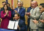 Florida Gov. Ron DeSantis hold up the signed legislation that seeks to punish social media platforms that remove conservative ideas from their sites, inside Florida International University's MARC building in Miami on Monday, May 24, 2021. (Carl Juste/Miami Herald via AP)