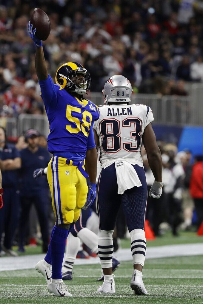 Los Angeles Rams' Cory Littleton (58) raises the football after intercepting a pass, in front of New England Patriots' Dwayne Allen (83) during the first half of the NFL Super Bowl 53 football game Sunday, Feb. 3, 2019, in Atlanta. (AP Photo/Frank Franklin II)