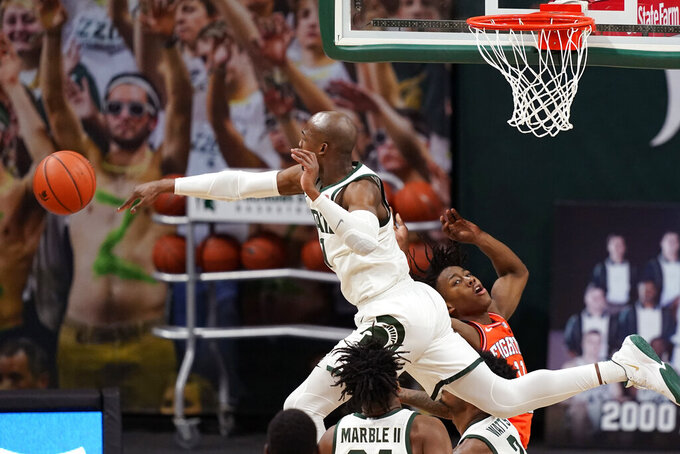 Michigan State guard Joshua Langford blocks an attempt by Illinois guard Ayo Dosunmu (11) during the second half of an NCAA college basketball game, Tuesday, Feb. 23, 2021, in East Lansing, Mich. (AP Photo/Carlos Osorio)