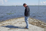 In this May 10, 2019 photo, Brett Adams stands where the road to his flooded farm disappears under flood waters, with the farm buildings visible in the background, in Peru, Neb. Adams had thousands of acres under water, about 80 percent of his land, this year. The water split open his grain bins and submerged his parents' house and other buildings when the levee protecting the farm broke. (AP Photo/Nati Harnik)