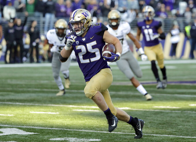 FILE - In this Oct. 20, 2018, file photo, Washington linebacker Ben Burr-Kirven (25) runs after he intercepted a pass thrown by Colorado quarterback Steven Montez during the second half of an NCAA college football game in Seattle. Burr-Kirven was named the Pac-12 defensive player of the year Thursday, Dec. 6, 2018. (AP Photo/Ted S. Warren, File)